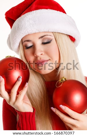 Portrait of a beautiful woman wearing a santa hat smiling with christmas red balls in her hands
