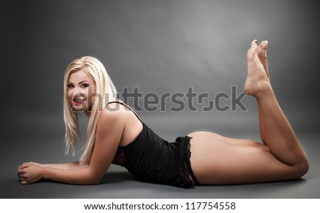 Portrait of a beautiful woman wearing lingerie while laying on the floor - stock photo