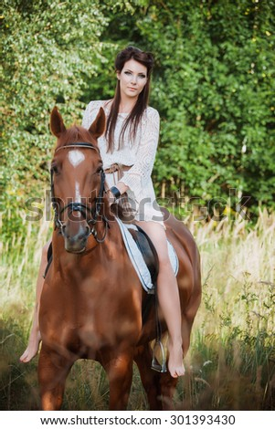 Portrait of a beautiful woman with a horse on nature