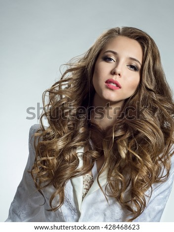 Portrait of a beautiful woman with a long curly hair in a white jacket