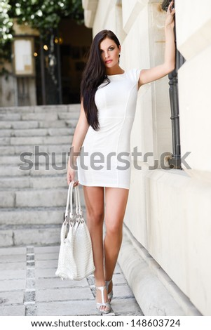 Portrait of a beautiful woman with bag in the street - stock photo