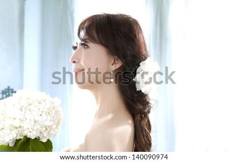 Portrait of a beautiful woman with bouquet of white flower - stock photo