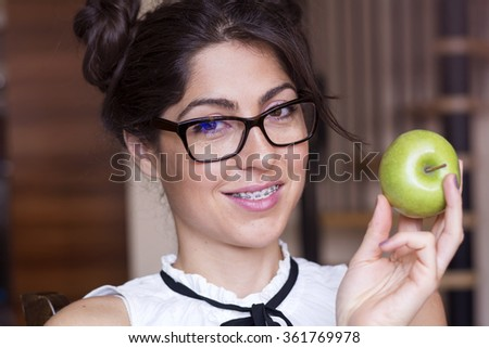 Portrait of a beautiful woman with braces on teeth eating green apple.Orthodontic Treatment. Dental care Concept - stock photo