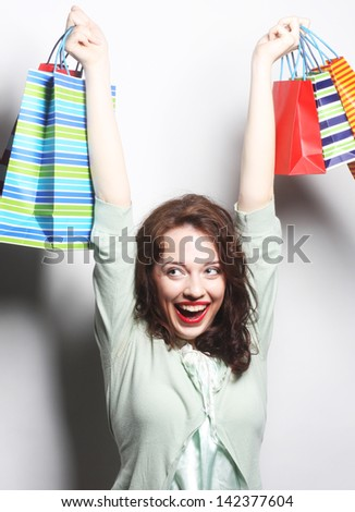 Portrait of a beautiful woman with colored shopping bags - stock photo