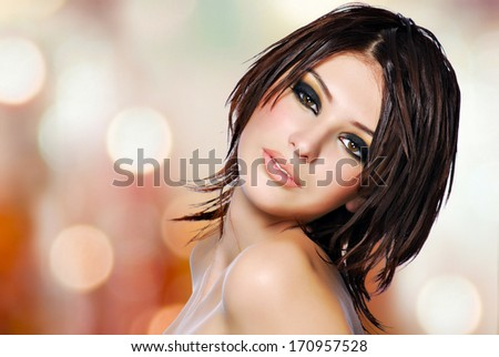 Portrait of a beautiful woman with creative hairstyle. Pretty female model  with fashion makeup over art night lights - stock photo