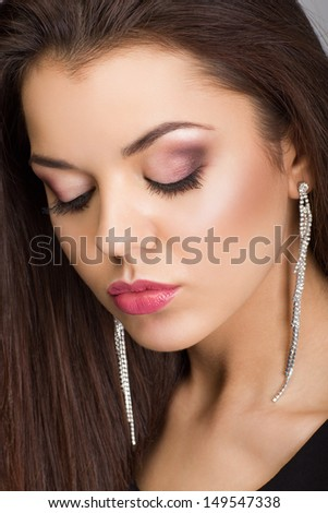 Portrait of a beautiful woman with evening make-up and earrings looking down