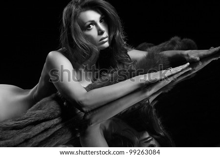 portrait of a beautiful woman with fur on a black background