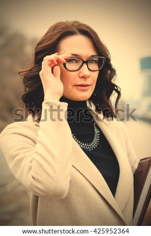 portrait of a beautiful woman with glasses. businesswoman, teacher. instagram image filter retro style - stock photo