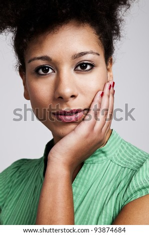 Portrait of a beautiful woman with hand on cheek. Studio shot.