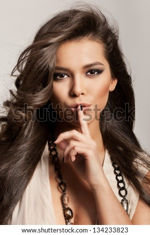 Portrait of a beautiful woman with healthy long brown hair and fresh makeup making a hush gesture. Wavy Hair. Hairstyle. Not isolated on grey background. Indoor