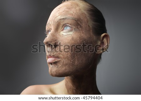 Portrait of a beautiful woman with her face covered with dried clay - stock photo