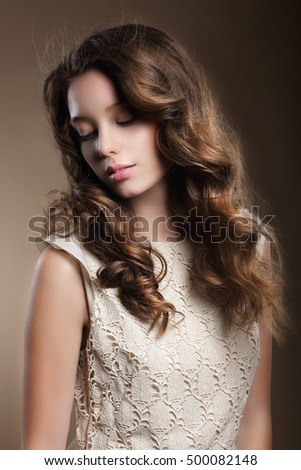 Portrait of a beautiful woman with long curly hair. Look down.