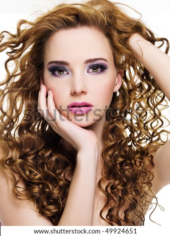 Portrait of a beautiful  woman with  long curly hairs - isolated on white - stock photo