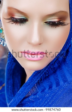 portrait of a beautiful woman with long false feather eyelashes and bright make-up wearing blue - stock photo