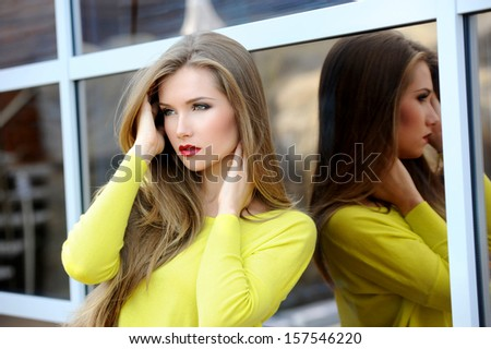 Portrait of a beautiful woman with long hair in a sweater outdoors - stock photo