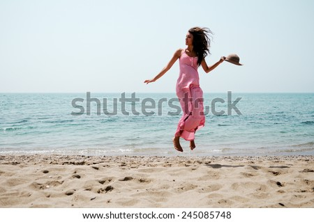 Portrait of a beautiful woman with long pink dress jumping on a tropical beach