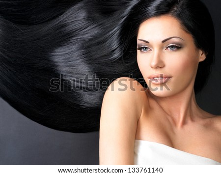 Portrait of a beautiful woman with long straight black hair lying on the dark background - stock photo