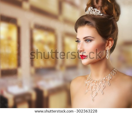 Portrait of a beautiful woman with makeup and elegant hairstyle on background jewelry store - stock photo