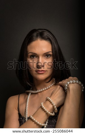 Portrait of a beautiful woman with pearls - stock photo