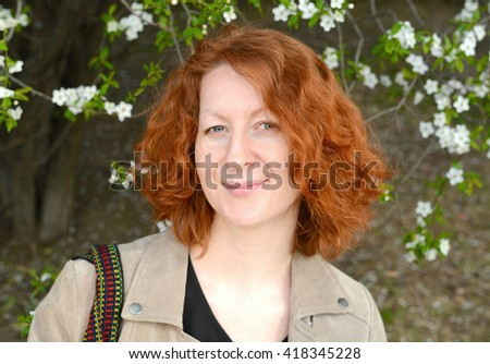 Portrait of a beautiful woman with red curly hair, on a background of a blossoming tree - stock photo