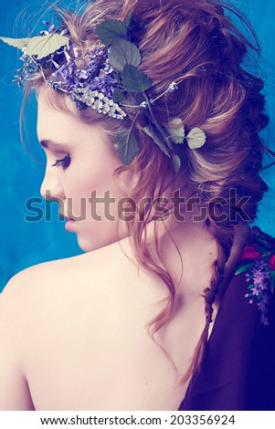 portrait of a beautiful woman with red hair in curly braided hairstyle wearing a crown of fresh flowers - stock photo