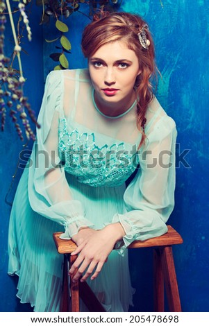 portrait of a beautiful woman with red hair in curly braided hairstyle. wearing a romantic blue turquoise dress on grunge blue background  - stock photo