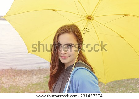 portrait of a beautiful woman with yellow umbrella - stock photo