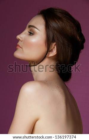 Portrait of a beautiful 30 year old brunette woman with bare shoulders and back wearing natural make-up on pink studio background - stock photo