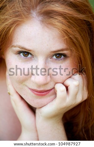 Portrait of a beautiful 20 year old redhead woman looking at camera and smiling.