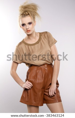 Portrait of a beautiful young adult attractive sexy and sensuality pretty blonde woman in brown dress isolated on light background - stock photo
