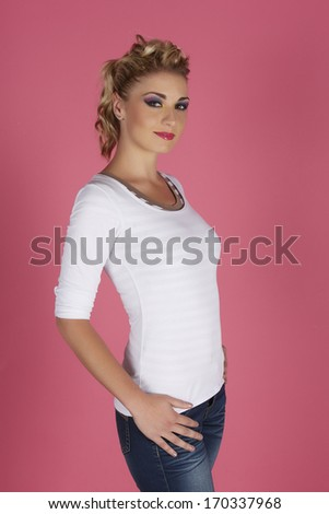 Portrait of a beautiful young adult caucasian woman with blonde hair and casual white shirt with glamorous makeup and a formal hairstyle on a pink background