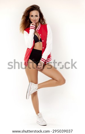 portrait of a beautiful young adult sensuality attractive and sexy pretty brunette cheerleader girl in black lingerie and red baseball jacket isolated on white background