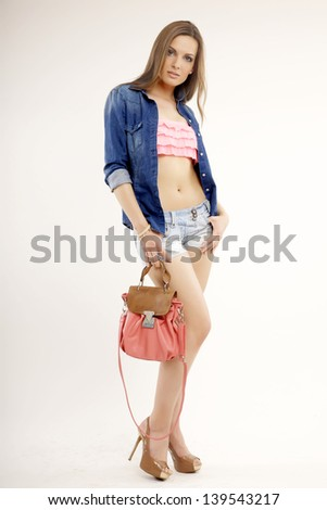 portrait of a beautiful young adult sensuality blonde woman in blue jeans with handbag isolated on white background