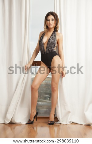 Portrait of a beautiful young adult slim sexy and attractive sensuality pretty brunette woman in black lingerie against the sunlight window - stock photo
