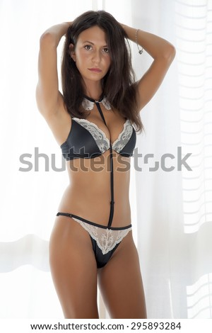 Portrait of a beautiful young adult slim sexy sensuality and attractive pretty brunette woman in black lingerie against the morning sunlight window - stock photo