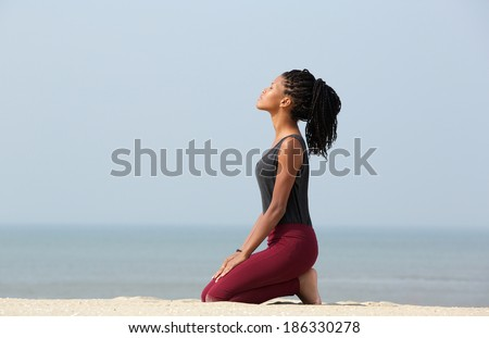 Portrait of a beautiful young african american woman meditating at the beach enjoying summer - stock photo