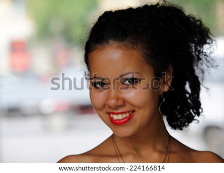 Portrait of a beautiful young African woman smiling, urban background - stock photo