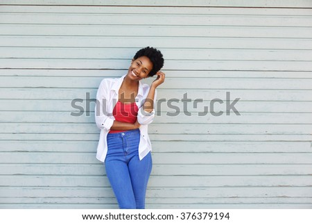 Portrait of a beautiful young african woman smiling with hand in hair against a white wall - stock photo