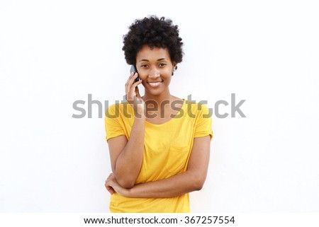 Portrait of a beautiful young african woman talking on cell phone against white background - stock photo