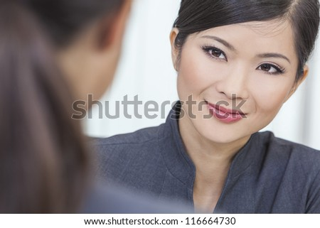 Portrait of a beautiful young Asian Chinese woman or businesswoman in office meeting with female colleague - stock photo