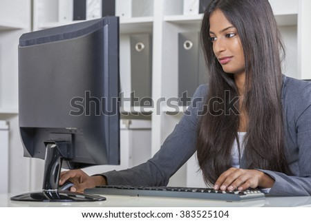 Portrait of a beautiful young Asian Indian woman or businesswoman in office typing using a computer - stock photo