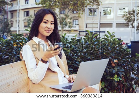 Portrait of a beautiful young asian well-dressed business woman holding on her portable laptop computer while sitting on a wooden bench and chatting on the smart-phone - stock photo