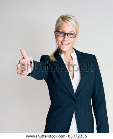 Portrait of a beautiful young blond business woman showing thumbs up. - stock photo
