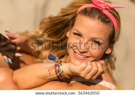 Portrait of a beautiful young blond, sitting on a sunbed on a beach and enjoying the sun - stock photo