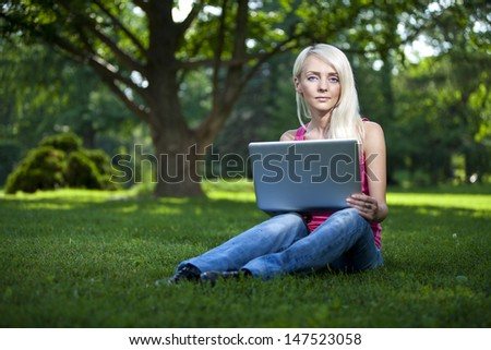 Portrait of a beautiful young blond woman sitting outdoor with laptop