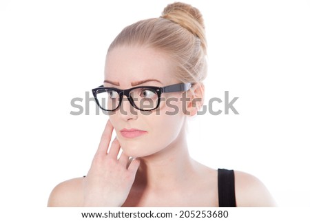 Portrait of a beautiful young blond woman, with loop of hair, wearing black framed eyeglasses, looking to the right with a pensive expression, on white - stock photo