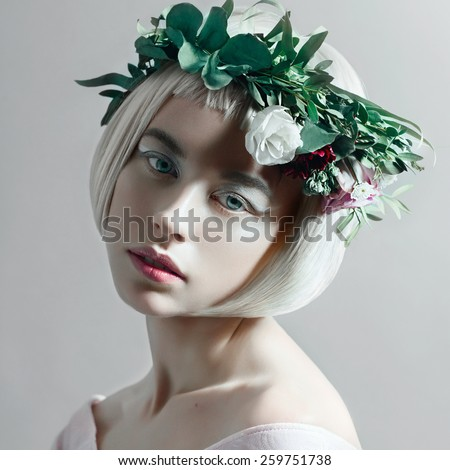 Portrait of a beautiful young blond woman with short hair and a wreath of flowers in the studio, close up