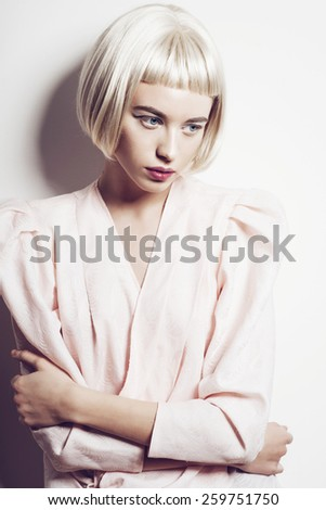 Portrait of a beautiful young blond woman with short hair in the studio on a white background - stock photo