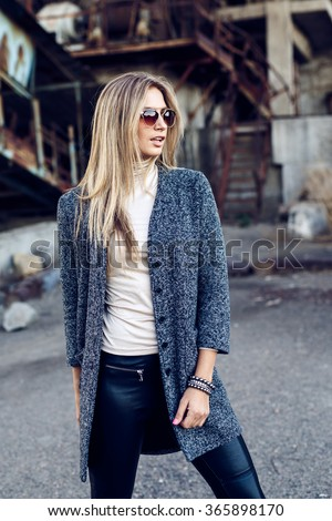 Portrait of a beautiful young blond womanin grey coat, sunglasses, leather pants in an industrial background. Abandoned metal factory.  - stock photo