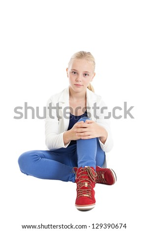 Portrait of a beautiful young blonde european girl. Girl wearing fashionable clothes sitting on the floor. Studio shot, isolated on white background.